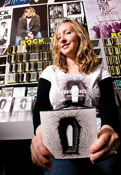 "Emily Charette ('07), pictured at Amoeba Records in San Francisco, is surrounded by the Death Magnetic Metallica CD cover she designed.  The CD recently earned a Grammy for ""best recording package."" (Photo by Patricia Mazzera)"