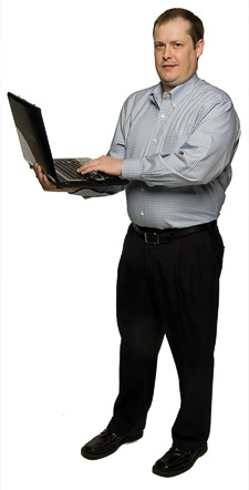 Daniel L. Spears standing with an open laptop computer. (Photo by Mike Woodruff)