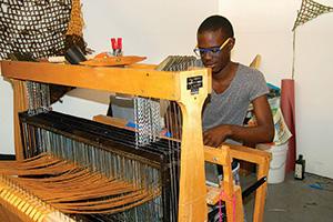 Diedrick Brackens ('11) works on his loom. (Photo by Sofia V. Gonzalez)
