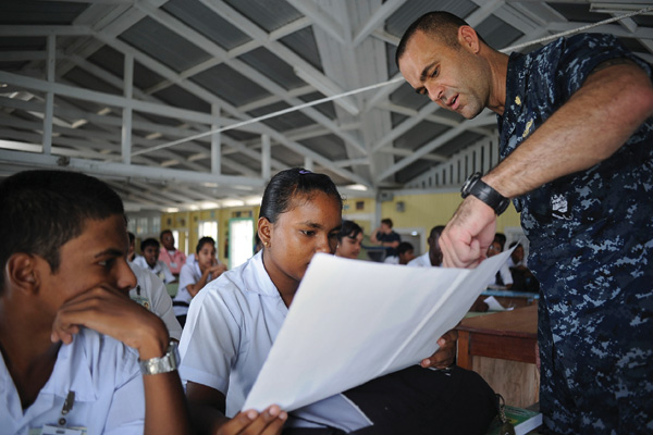 Lt. Michael  Kavanaugh ('05,'08 M.S.) speaks to school children in Guyana about mosquitoes that carry  infectious diseases, during a Continuing Promise 2010 community service event. (Courtesy of Oscar Sosa/U.S. Navy)