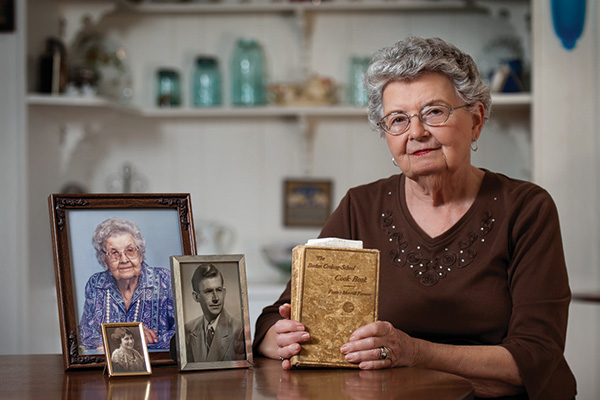 Ruth Ann Davison Torgerson ('50) is pictured with photos of her aunt, mother and husband and the Fannie Farmer cookbook that was a North Texas textbook almost a century ago. (Photo by Gary Payne)