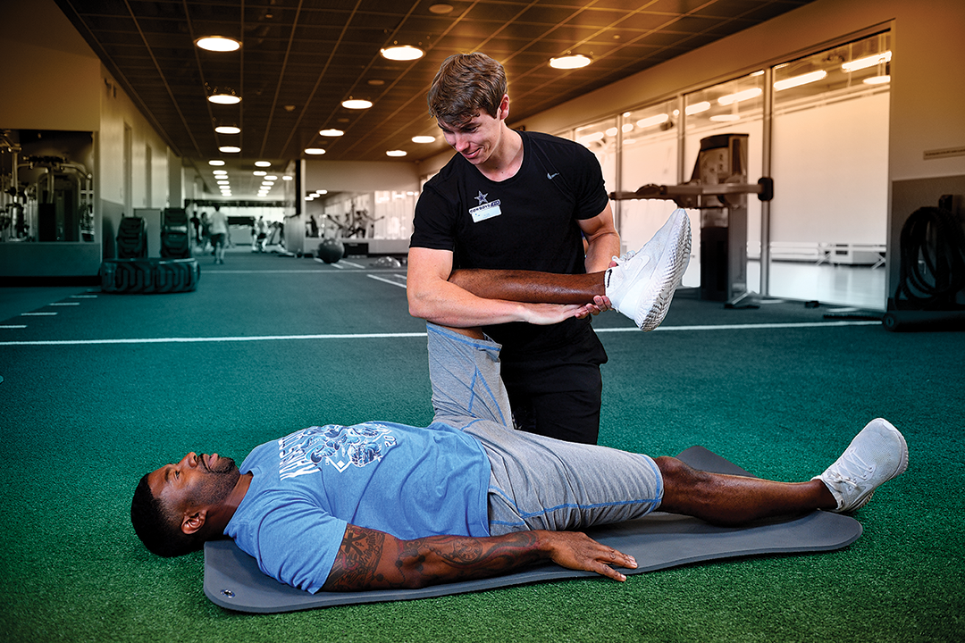 Alex Shaw assisting an athlete with leg extensions