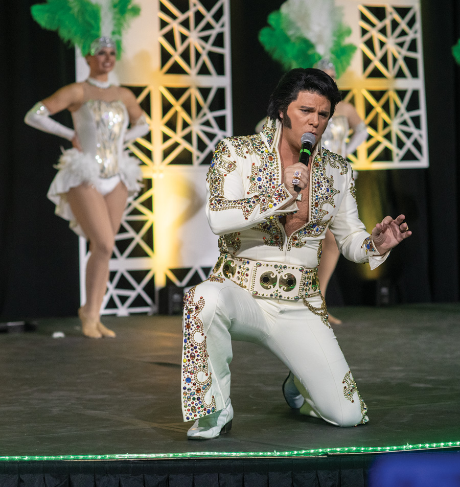Elvis impersonator with Las Vegas style showgirls in the background