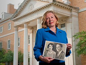 Pat Guseman is pictured with a photo of her mother and father, Vera and Ulys G. Knight ('25), in front of the Hurley Administration Building. (Photo by Jonathan Reynolds)