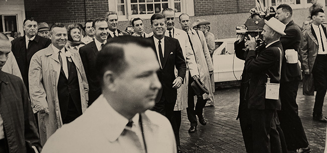 Mike Howard ('60), foreground, leaving the Texas Hotel in Fort Worth with President John F. Kennedy, Vice President Lyndon B. Johnson and other government officials. (Courtesy of Mike Howard)