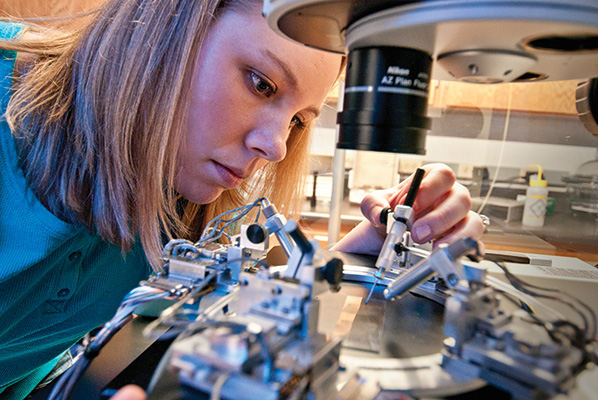 Kristina Clemons works with the nanomanipulator developed by Guido Verbeck, associate professor of chemistry. (Photo by Jonathan Reynolds)