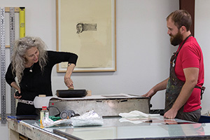 Printmaking master's student Preston Bradley, right, shows Kiki Smith, left, the capabilities of the P.R.I.N.T. Press equipment during a visit this fall. (Photo by Ann Graham)