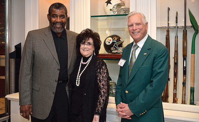 """""""Mean"""" Joe Greene, one of the 2013 alumni honorees, with Sara Sue and Don ('63) Potts at their home in Dallas during the Emerald Eagle Honors Kickoff event they hosted in November. (Photo by Michael Clements)"""