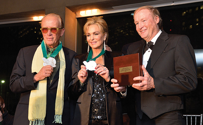 2014 alumni honorees Peter Weller ('70) and Phyllis George with George Getschow, principal lecturer in the Frank W. and Sue Mayborn School of Journalism, accepting for Larry McMurtry ('58). (Photo by Michael Clements)