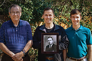 From left, John Bowman Harvill Jr. ('55, '57 M.S.), John Bowman Harvill III holding a portrait of his grandfather, John Bowman Harvill Sr. ('30) and John Bowman Harvill IV.(Photo courtesy of the Harvill Family)