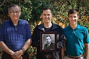 From left, John Bowman Harvill Jr. ('55, '57 M.S.), John Bowman Harvill III holding a portrait of his grandfather, John Bowman Harvill Sr. ('30) and John Bowman Harvill IV.(Photo courtesy of the Harvill Family)