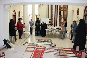 Sheikha Altaf Al-Sabah, at left in red, helped organize the collaboration between UNT faculty member Lesli Robertson, at right with brown scarf, and Al Sadu House in Kuwait. After Robertson's workshop with Al Sadu House, the weavers gathered to view samples of their new designs alongside traditional designs. (Photo courtesy of Patricia Redding)