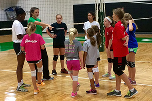 Assistant coach Madison Barr, in green, coaches a volleyball camp. (Photo by T.C. Greene)