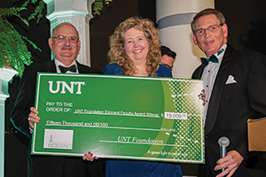Angela Wilson, Regents Professor of chemistry, receives the Eminent Faculty Award cash prize from UNT Foundation board member Bob Sherman and President and CEO of the UNT Foundation Mike Mlinac. (Photo by Ahna Hubnik)