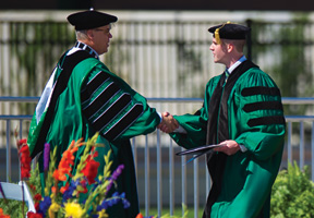 President Neal Smatresk welcomes speaker Steven Davidson ('15) at University-wide Commencement. (Photo by Gary Payne)