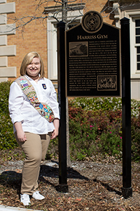 Elise Clements beside the Harriss Gym campus historical sign