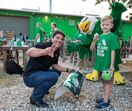 Join the UNT Alumni Association for family-friendly events like this spring's Coaches Caravan where Mean Green head football coach Seth Littrell met UNT fan Lukas Kamenicky.