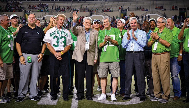 Legendary Mean Green head coach Hayden Fry (waving) and some of his former Mean Green players were honored at halftime of the UNT game against UTSA in October. Fry led the football team from 1973 to 1978, during which time the Mean Green had four straight winning seasons, including a 10-win season and a national ranking in 1977. (Photo by Michael Clements)
