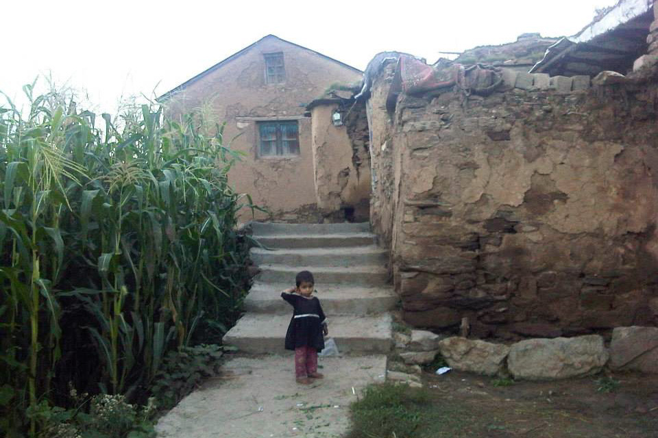 Child standing in front of a stone building