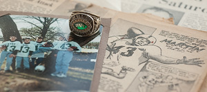 "Cecil ""Zeke"" Martin's ('51,'51 M.Ed.) North Texas Athletic Hall of Fame ring amid memorabilia and  a photo of his five grandsons, all wearing his North Texas jersey No. 43. (Photo by Angilee Wilkerson)"