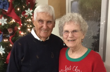 Photo of Fred and Mae Bruce in front of a Christmas tree