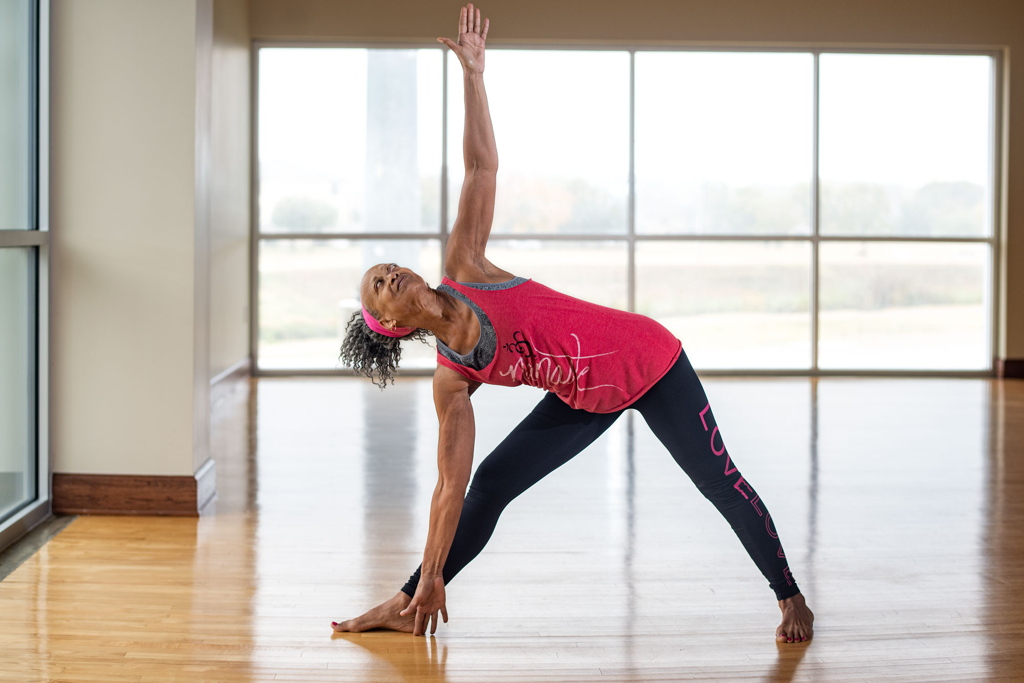 Patricia Ebaire does an extended triangle pose during her yoga class.