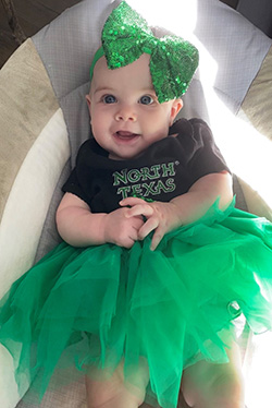 """Photo of Evie McNamara at six months wearing green hairbow, black T-shirt with """"North Texas"""" text and green tulle skirt"""