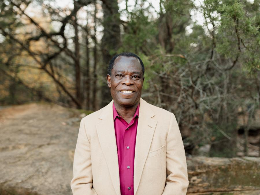 Joseph Oppong stands in a pink shirt and beige jacket in front of a group of trees.