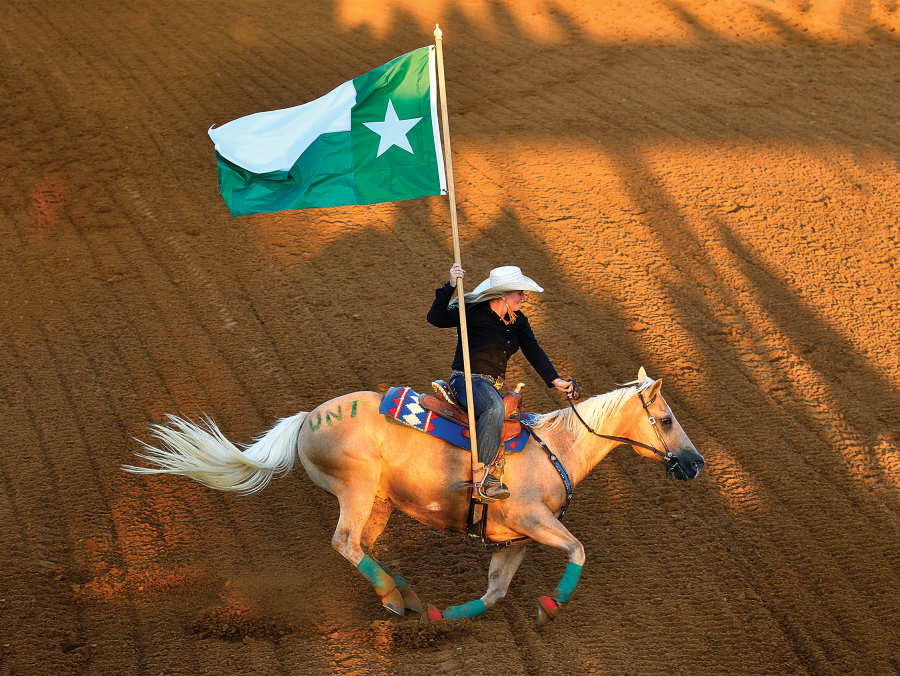 Man on horse back holding a UNT flag