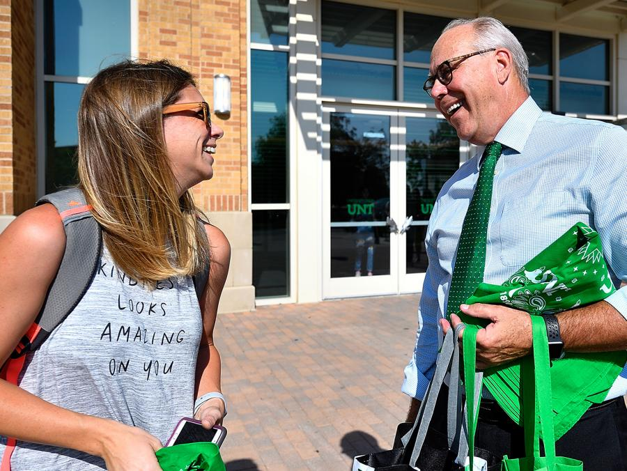 <p>President Neal Smatresk greeted students on the first day of school, giving away UNT gear on a Trivia Tram. (Photo by Michael Clements)</p>