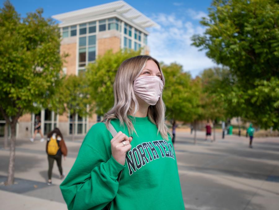 Blond female student in green North Texas sweatshirt walks in front of the University Union holding a bag.