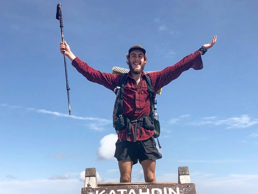 Brett Luce stands on top a sign for the Katahdin Baxter peak