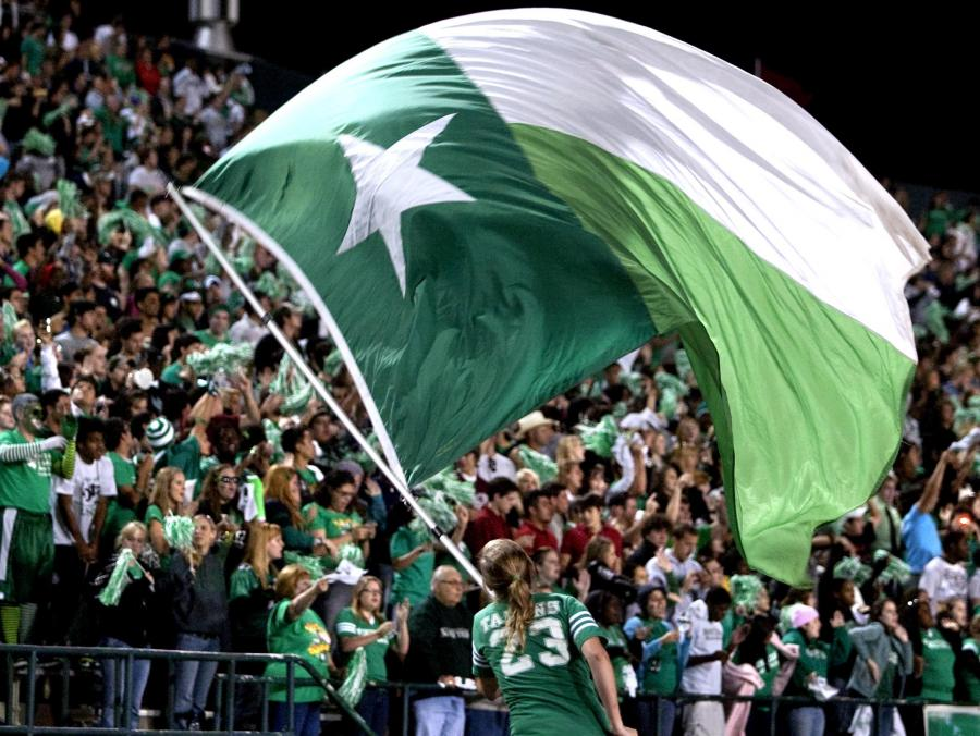 <p>Student waving UNT flag at football game</p>