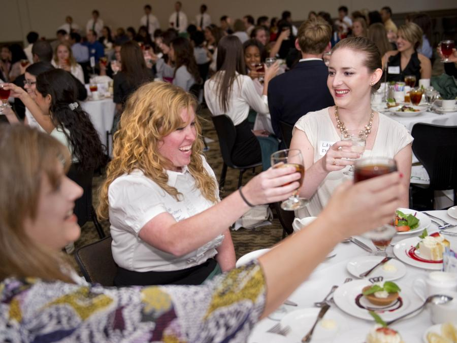 <p>Students toasting at etiquette dinner</p>
