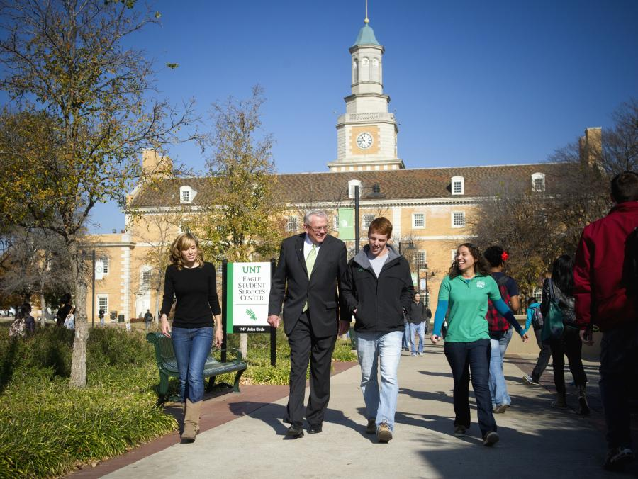 <p>President Lane Rawlins walking with students on campus</p>