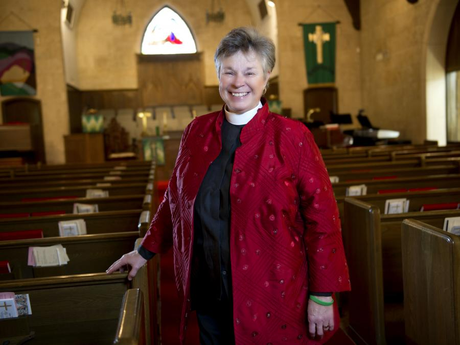 <p>Carol West standing in church sanctuary</p>