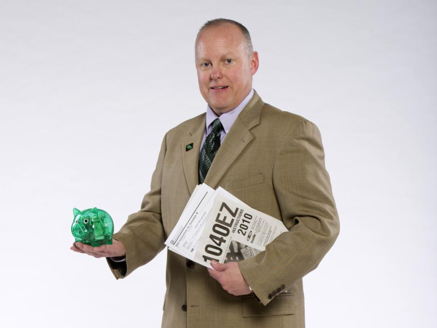 Paul F. Goebel holding piggy bank and tax forms