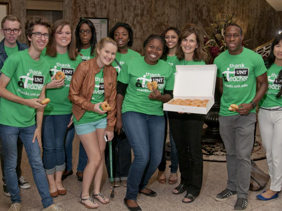 <p>Students standing with box of doughnuts</p>