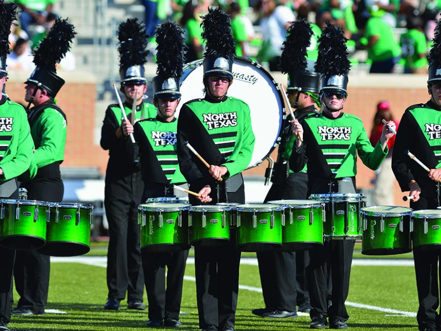 <p>Green Brigade drumline performing at game</p>