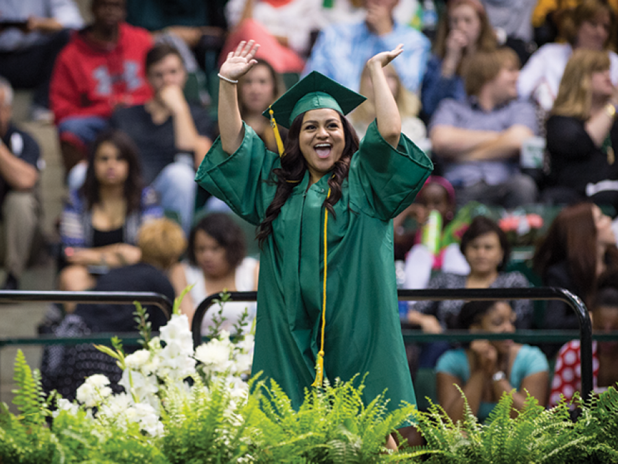 UNT student on stage at commencement wear cap and gown regalia