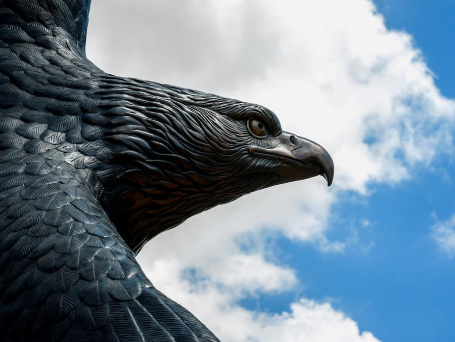 Bronze Eagle statue against a blue sky.