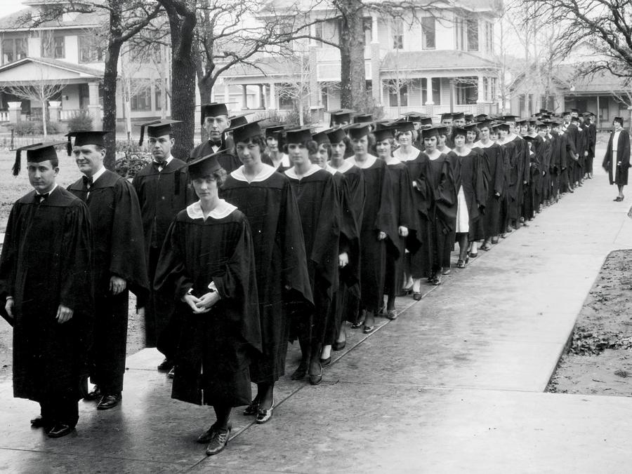 Graduates line up on campus in the 1920s.