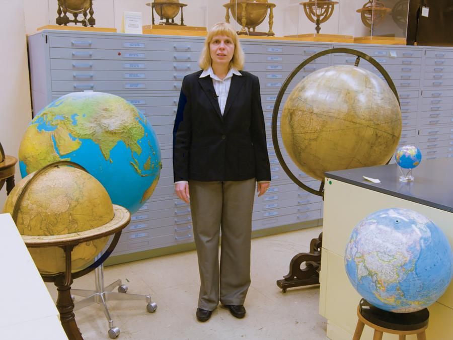 Paulette Marie Hasier standing with numerous globes and file cabinets