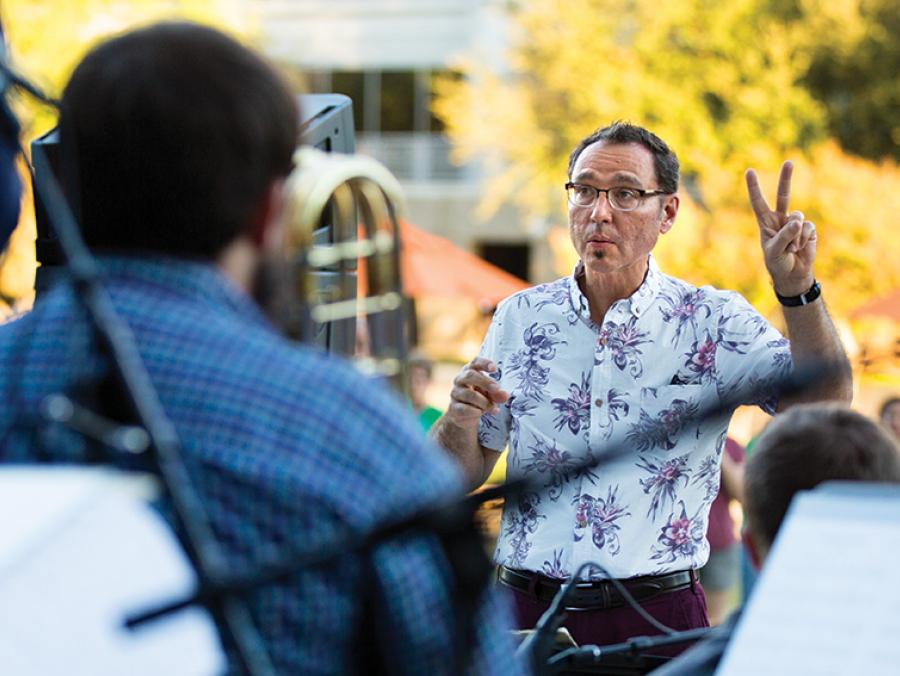 <p>Alan Baylock conducting an outdoor performance ath the Frisco Art Walk</p>