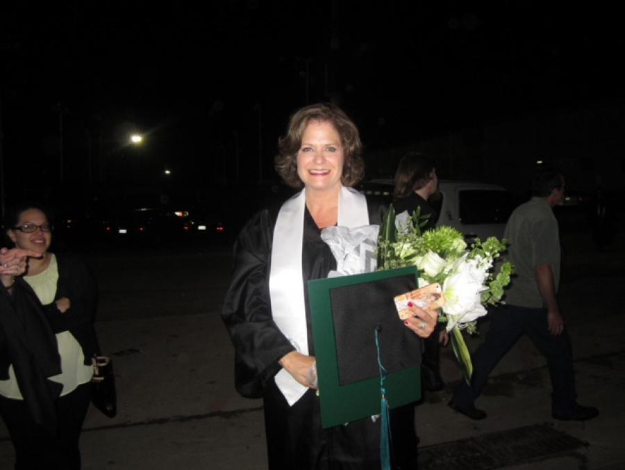 Janet Bracken at commencement in cap and gown regalia