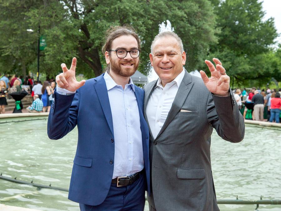 John Solis with his father, Javier making the UNT eagle claw in front of the library mall fountain