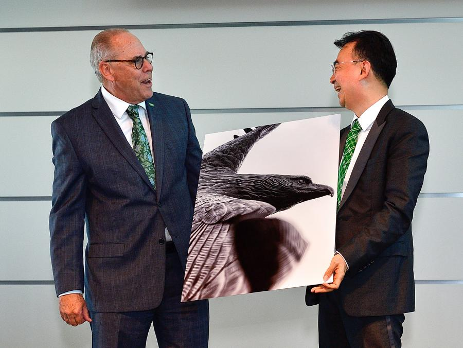 <p>President Neil Smatresk presents NetDragon founder Dejian Liu with an eagle painting at the NetDragon Digital Research Centre launch announcement May 15. The centre will offer students and faculty sponsored research and technology development opportunitie</p>