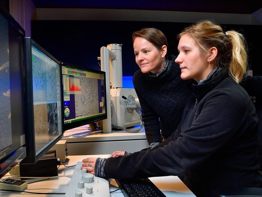Two women at a a series of computer monitors
