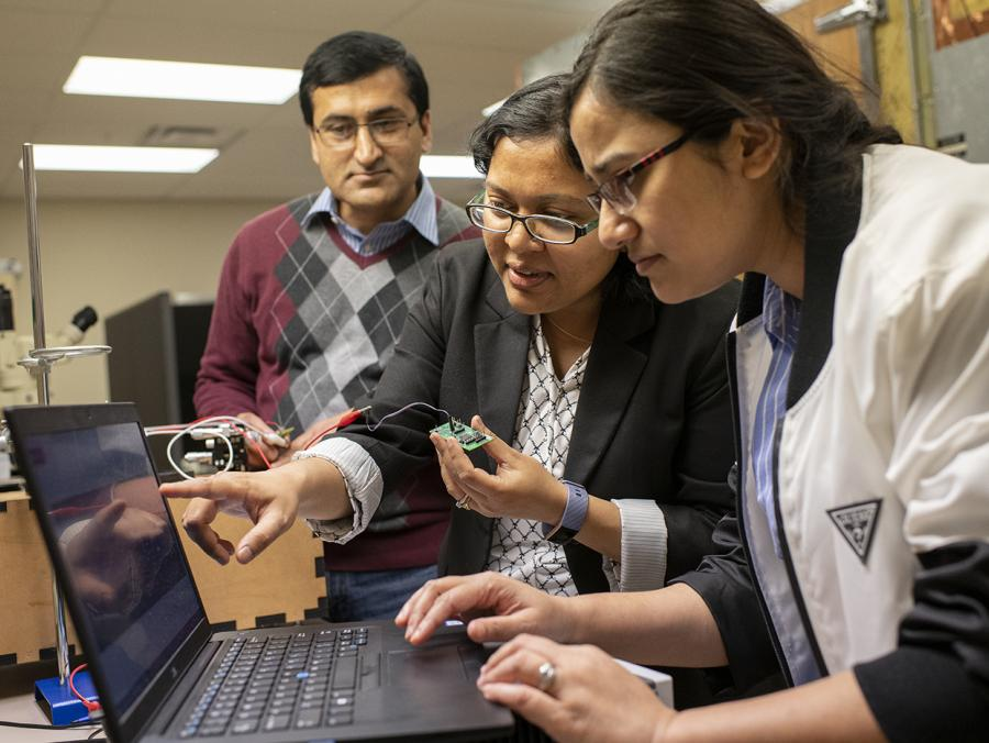 Electrical Engineering Assistant Professor Ifana Mahbub (center) works with Ph.D. students Pashupati Adhikari (left) and Nishat Tasneem on her electro-wetting project.