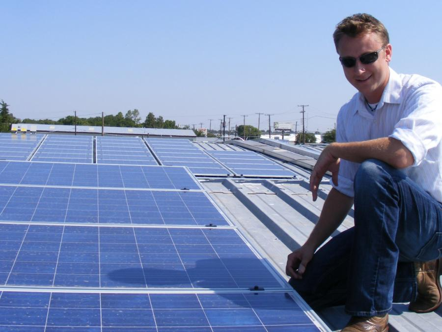 <p>James Clayton Lane sitting on top of solar panels</p>
